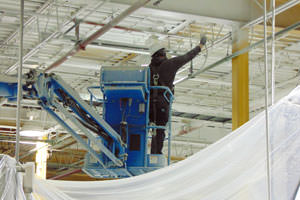 worker spray painting metal ceiling trusses at a Pickering, ON plant