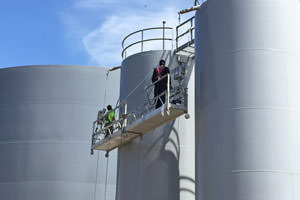 Guelph industrial painters spray painting large steel tanks