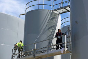 workers spray painting steel storage tanks in Oakville, Ontario