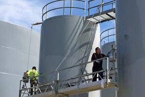 workers spray painting steel storage tanks in Oakville, Ontario
