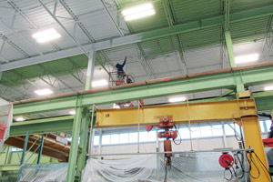 Toronto spray painter working on steel beams and metal ceiling in a factory