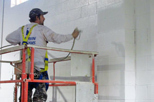 Newmarket painter spraying a commercial building wall