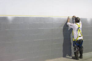 Brantford painter masking and spray painting a commercial building wall